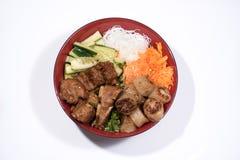 Kom van het broodje van rundvleesbo met salade, varkensvleesribben, verse kruiden Stock Fotografie