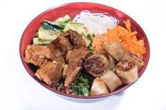 Kom van het broodje van rundvleesbo met salade, varkensvleesribben, verse kruiden Royalty-vrije Stock Afbeeldingen