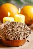 Kom van Kerstmiskoekjes onder aromatische sinaasappelen en gele cand Stock Foto