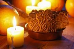 Kom van Kerstmiskoekjes onder aromatische sinaasappelen en gele cand Stock Fotografie