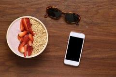 Kom van muesli en smartphone op een houten lijst stock foto's
