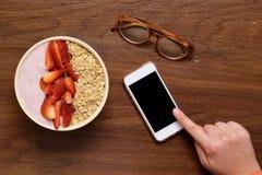 Kom van muesli en smartphone op een houten lijst stock foto