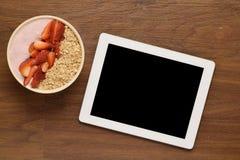 Kom van muesli en tabletgadget op een houten lijst Stock Foto