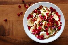 Kom van ontbijthavermeel met granaatappel, bananen, zaden en noten Stock Afbeeldingen