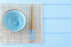 Kom voor sushi en stokken op een schone blauwe lijst Stock Foto's