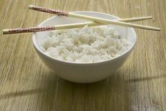 Kom witte rijst met eetstokjes, houten achtergrond royalty-vrije stock afbeelding