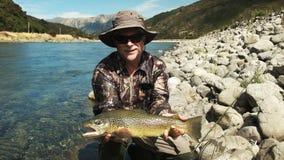 Komarnica rybak trzyma brown pstrąg