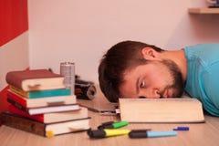 Komatöser Student mit seinem Kopf, der mitten in einem großen Buch liegt Lizenzfreies Stockfoto
