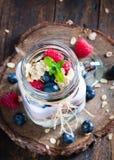Kombinerad frukt och yoghurt i exponeringsglas med lantlig bakgrund Fotografering för Bildbyråer
