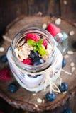 Kombinerad frukt och yoghurt i exponeringsglas med lantlig bakgrund Arkivbild
