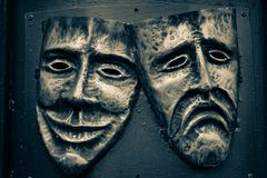 Komedie en tragediestaalmaskers die in gouden en donkerblauwe kleuren worden geschilderd stock fotografie