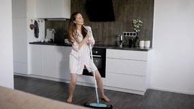 Komediförfattarekvinnan dansar med golvmopp under lokalvårdkökrum i hennes hus på ferier som sjunger och flyttar sig som är rolig