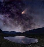 Komeet over bergmeer Stock Foto