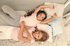 komfort hem- komfort f?r sm? flickor sm? flickor ?r lyckliga tillsammans tycka om home tid arkivbilder