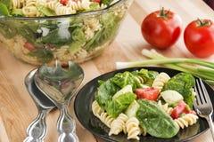 Komhoogtepunt van spinazie en rotinideegwarensalade stock afbeelding