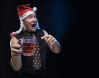 Komicznego aktora mężczyzna w nakrętce z warkoczami z szkłem piwo, w oczekiwaniu na boże narodzenia i nowego rok fotografia royalty free
