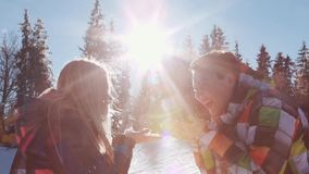 Komicznie potomstwa dobierają się w zima sporta odzieży Pogodny zima dzień, radosna blondynki dziewczyna i chłopiec podmuchowy śn zbiory wideo