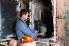 Komicznie samiec z glazurującą ceramiczną wazową pozycją blisko do Obrazy Royalty Free
