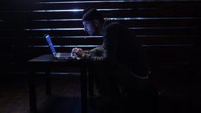 Komiczny śmieszny hacker popełnia cyber ataka z laptopem i pistoletem w jego ręki zbiory wideo