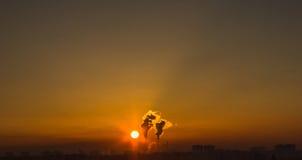 Kominy i zmrok dymią nad fabryką przy zmierzchem Zdjęcia Royalty Free