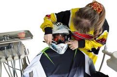 Komisch, behandelt Mädchenzahnarzt einen Patienten in einem Sturzhelm Lizenzfreie Stockfotografie