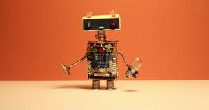 Komischer Roboterheimwerker geht und seine Arme rüttelnd Spielzeug Cyborg mit Glühlampeschraubenzieher Orange Wandgelbboden stock footage