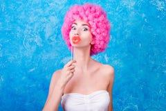 Komisches Mädchen/Frau/Jugendlicher des blauen Auges mit rosa gelockter Perücke ist wir Lizenzfreie Stockfotos