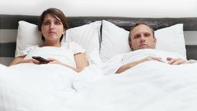 Komisk plats - fru- och makeTVfjärrkontroll kämpar i säng