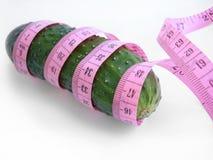 Komkommer met roze meetlint over witte achtergrond Stock Afbeeldingen