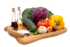 Komkommer, peper, ui, knoflook, koolbladeren, tomaat en rode kool op een plateau met olie, azijn, peper en zout Stock Afbeeldingen