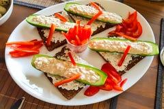 Komkommerboot met verse quark, peperstroken op zwart brood stock afbeeldingen