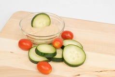 Komkommerplakken en tomaten met hummus royalty-vrije stock afbeelding