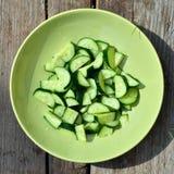 Komkommers in een groene plaat op houten achtergrond Stock Foto