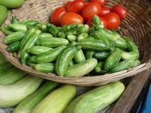 Komkommers en tomaten in een mand Stock Fotografie