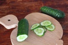 Komkommers op houten achtergrond Gesneden komkommer royalty-vrije stock foto's