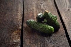 Komkommers, vers geplukte groene komkommers op een houten achtergrond stock fotografie