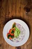 Komkommersalade, radijs, peper en peterselie op een houten achtergrond Stock Foto