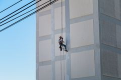 Kommande down för målare fasaden av en byggnad som rappelling med ett r Royaltyfri Foto