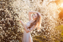 kommande fjäder Den lyckliga härliga unga kvinnan som kopplar av i blomning, parkerar Royaltyfri Bild