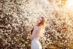 kommande fjäder Den lyckliga härliga unga kvinnan som kopplar av i blomning, parkerar Arkivbild