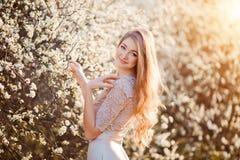 kommande fjäder Den lyckliga härliga unga kvinnan som kopplar av i blomning, parkerar Royaltyfri Foto