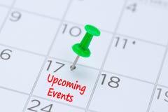 Kommande händelser som är skriftliga på en kalender med ett grönt pushstift till r Royaltyfria Foton