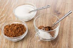 Kommen met cacaopoeder, lepel in kom met suiker, cacao, suiker in kop, lepel op lijst royalty-vrije stock afbeelding
