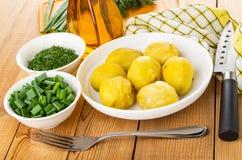 Kommen met gehakte dille en sjalot, servet, aardappelen in de schil in plaat, mes, vork op houten lijst stock fotografie