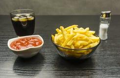 Kommen met gezouten frieten en ketchup en een glas kola w stock afbeeldingen