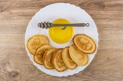 Kommen met honing, stok en pannekoeken in witte schotel Stock Fotografie