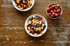 Kommen van gezonde organische muesli met vruchten op donkere houten lijst Stock Afbeeldingen