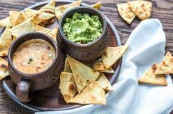 Kommen van guacamole en queso met tortillaspaanders Stock Foto