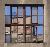 Kommersiell byggnad reflekterad i ett glass fönster Arkivfoto