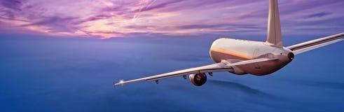 Kommersiell flygplanjetflygplan som flyger ovannämnda moln i härlig su Royaltyfri Bild
